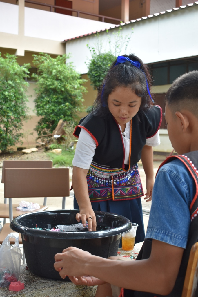 children at small village school making and selling candles learning skills for tourism in the jungle near. chiang mai thailand